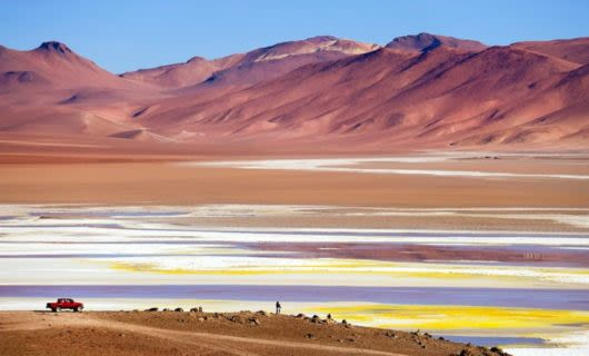 Truck sits in front of multicolored desert and mountains