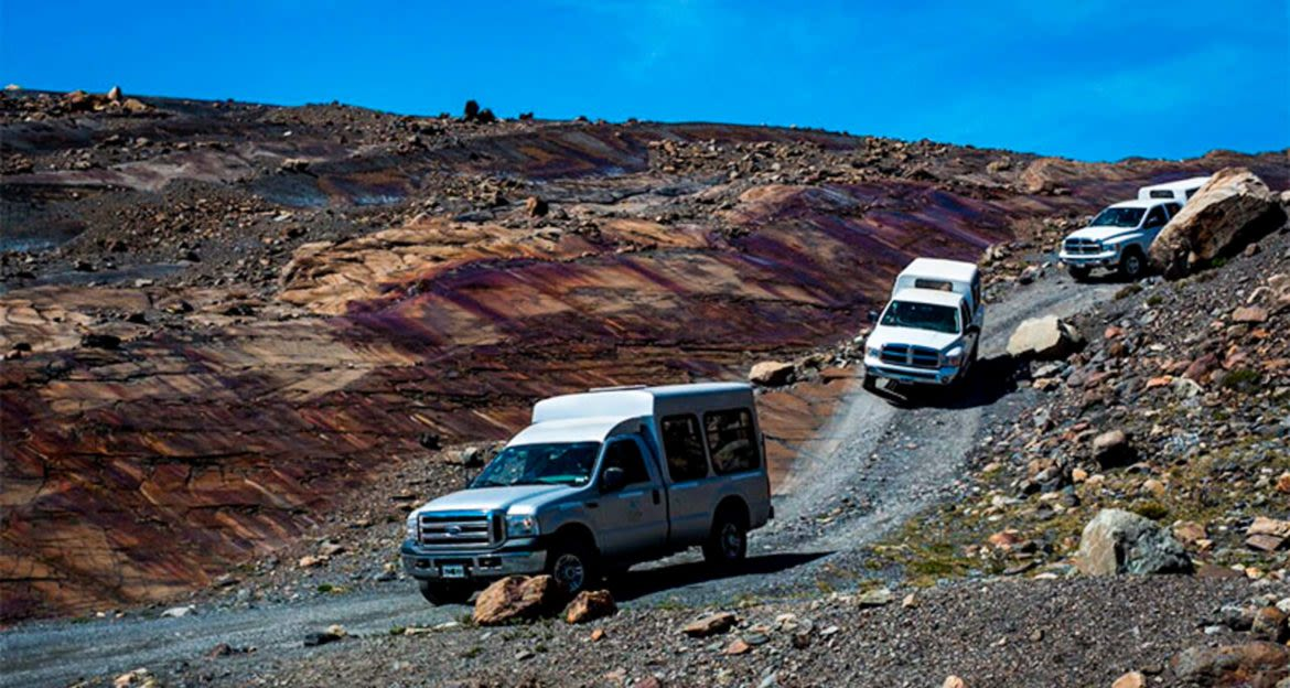 Three trucks drive down rocky desert road