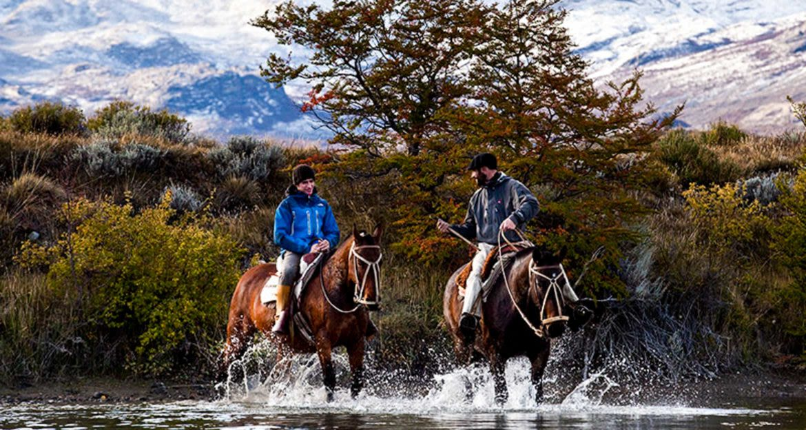 Two people ride horses through river