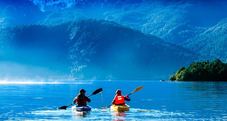 Two kayakers on mountain lake