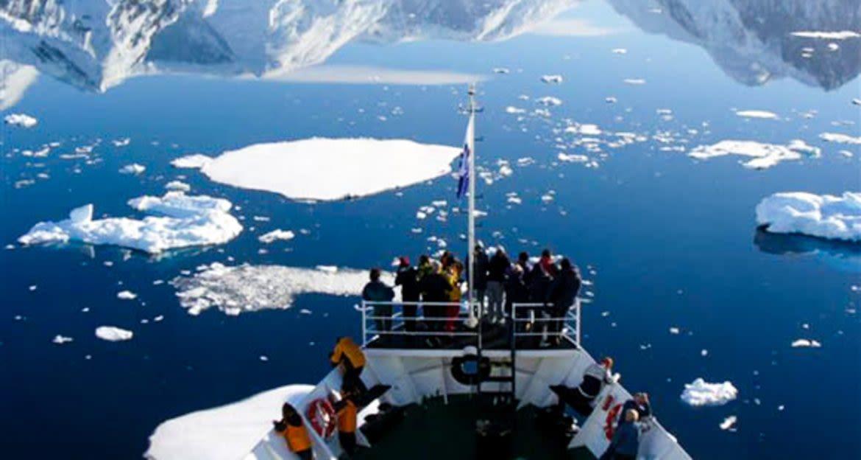 Ushaia Cruise travelers stand on deck of ship