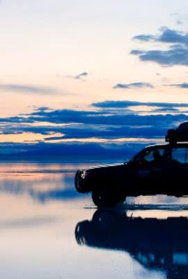 Car sits on Bolivia salt flats at evening