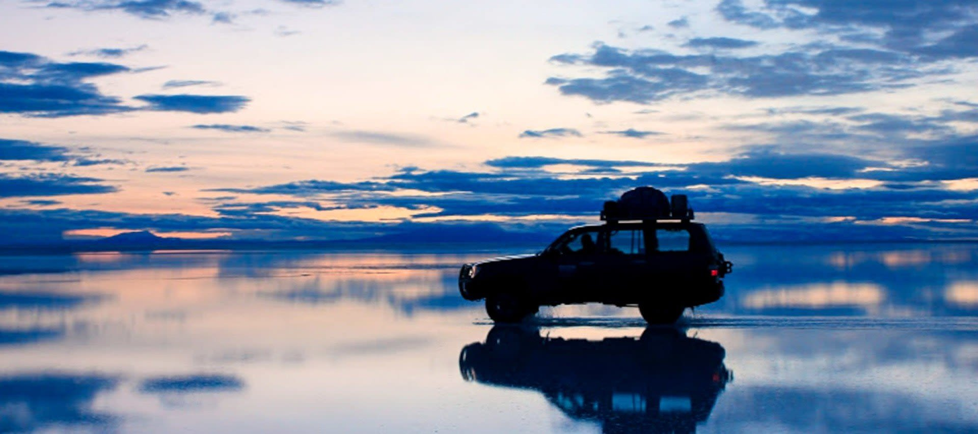 Car sits on Bolivia salt flats at evening