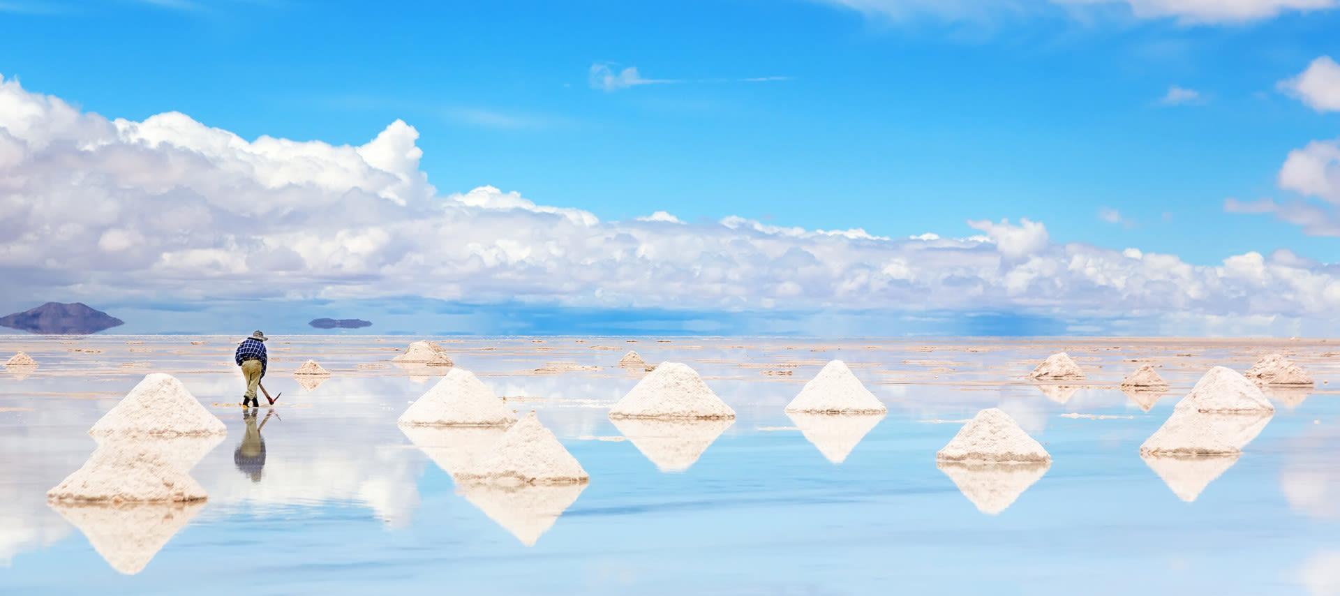 man harvesting salt at salar de uyuni