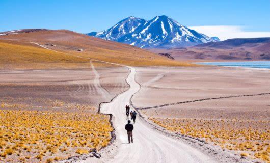Travelers walk down road leading toward mountain