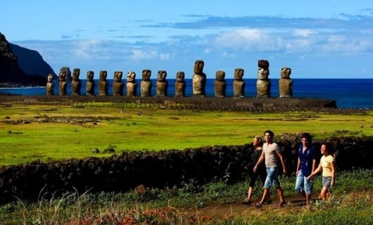 Group of travelers walk past statues on Easter Island