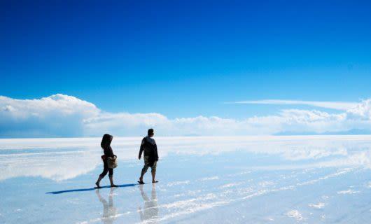 Two people walk across salt flats
