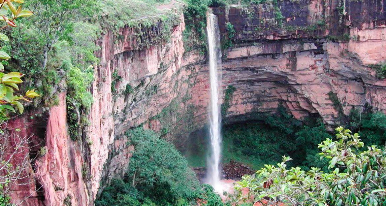 Waterfall runs down red rock