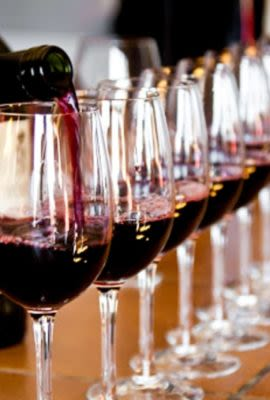 Person pouring wine into row of glasses