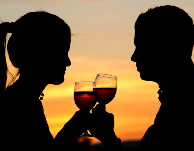 Silhouetted couple drink wine at sunset