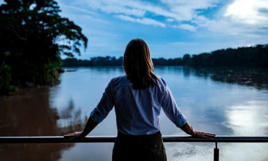 Woman stands on Amazon river cruise ship deck at evening