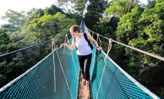 Woman crosses rope bridge in Amazon