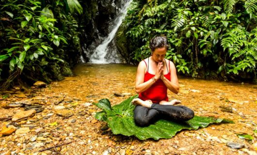 Woman sits on large leaf near waterfall to do yoga