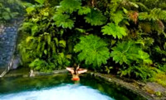 Woman sits in outdoor forest pool