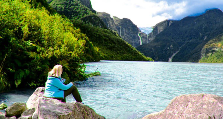 Woman sits on rock near mountain lake