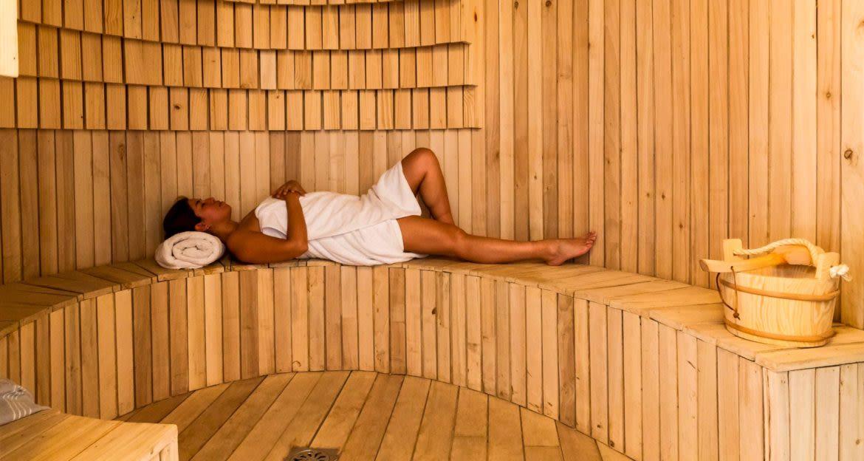 Woman lies on bench in sauna