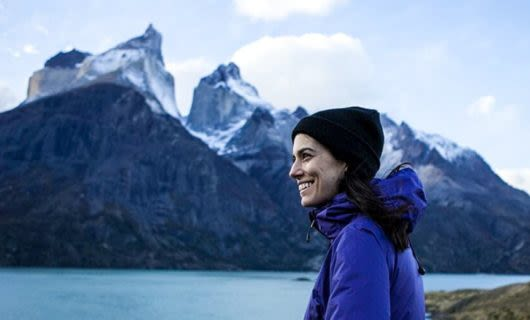 Smiling woman stands in front of Patagonia mountains