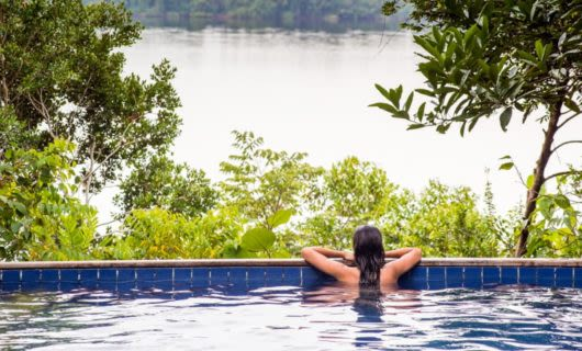 Woman sits at edge of Anavilhanas Jungle Lodge pool