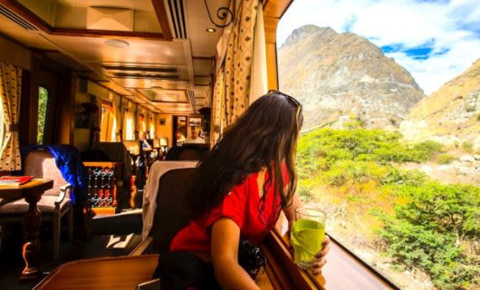 Woman enjoying drink and views on vintage train