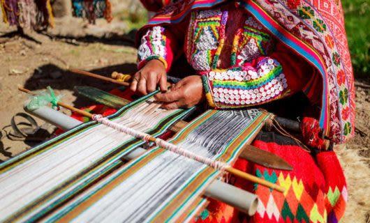 Woman weaves on loom in South America