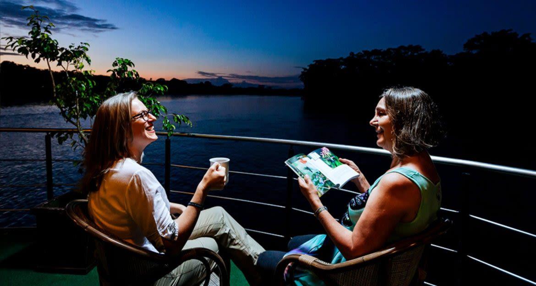 Women sit on cruise ship deck at night
