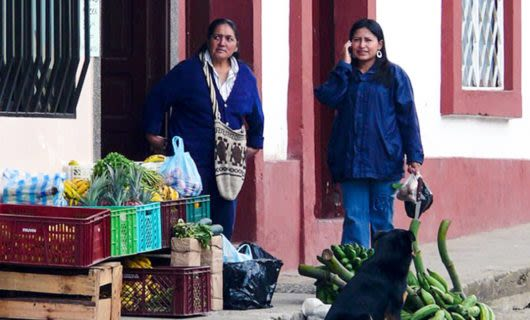 Two women and a dog stand on South America street