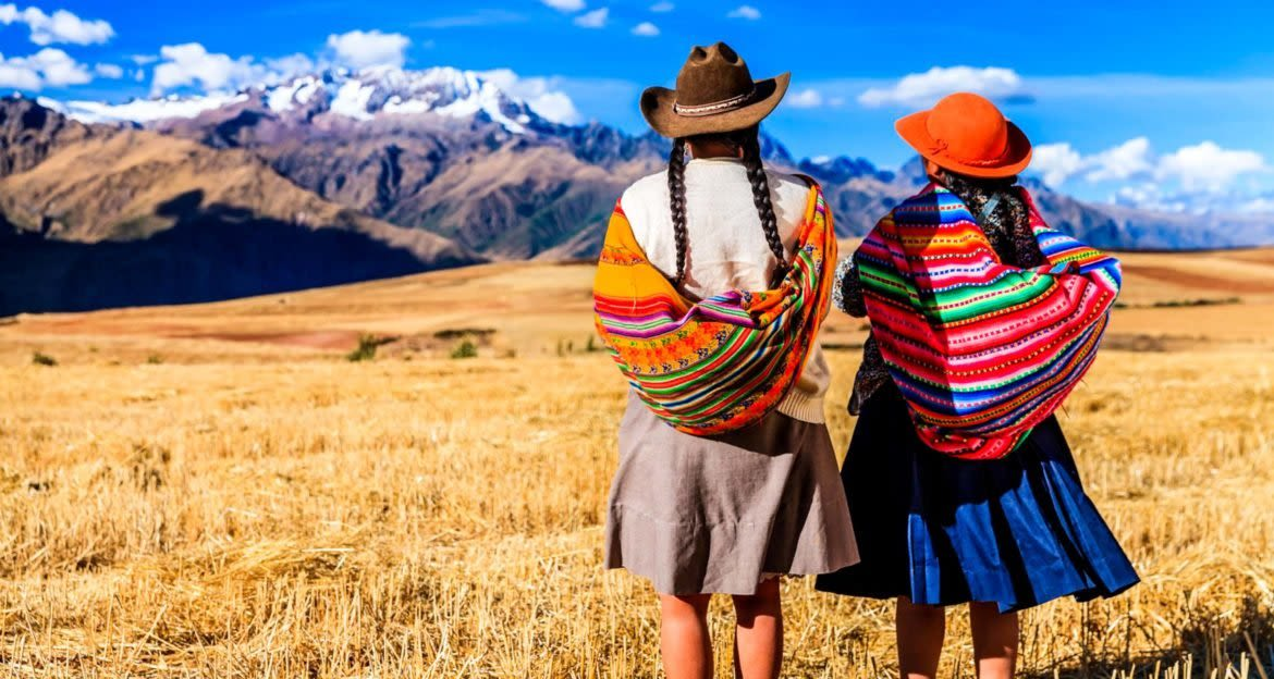 Two women din colorful shawls stand on Peru plain