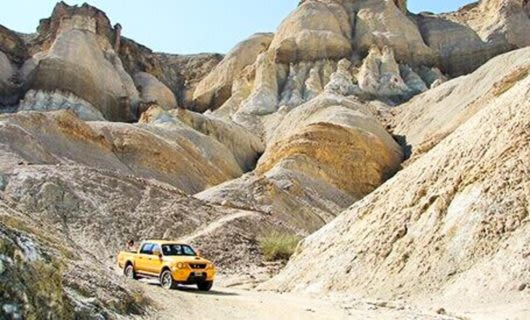 Yellow truck drives through rocky South America valley