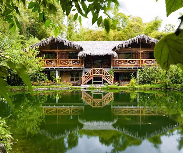 scenic Amazon Rainforest Lodge reflecting off pond