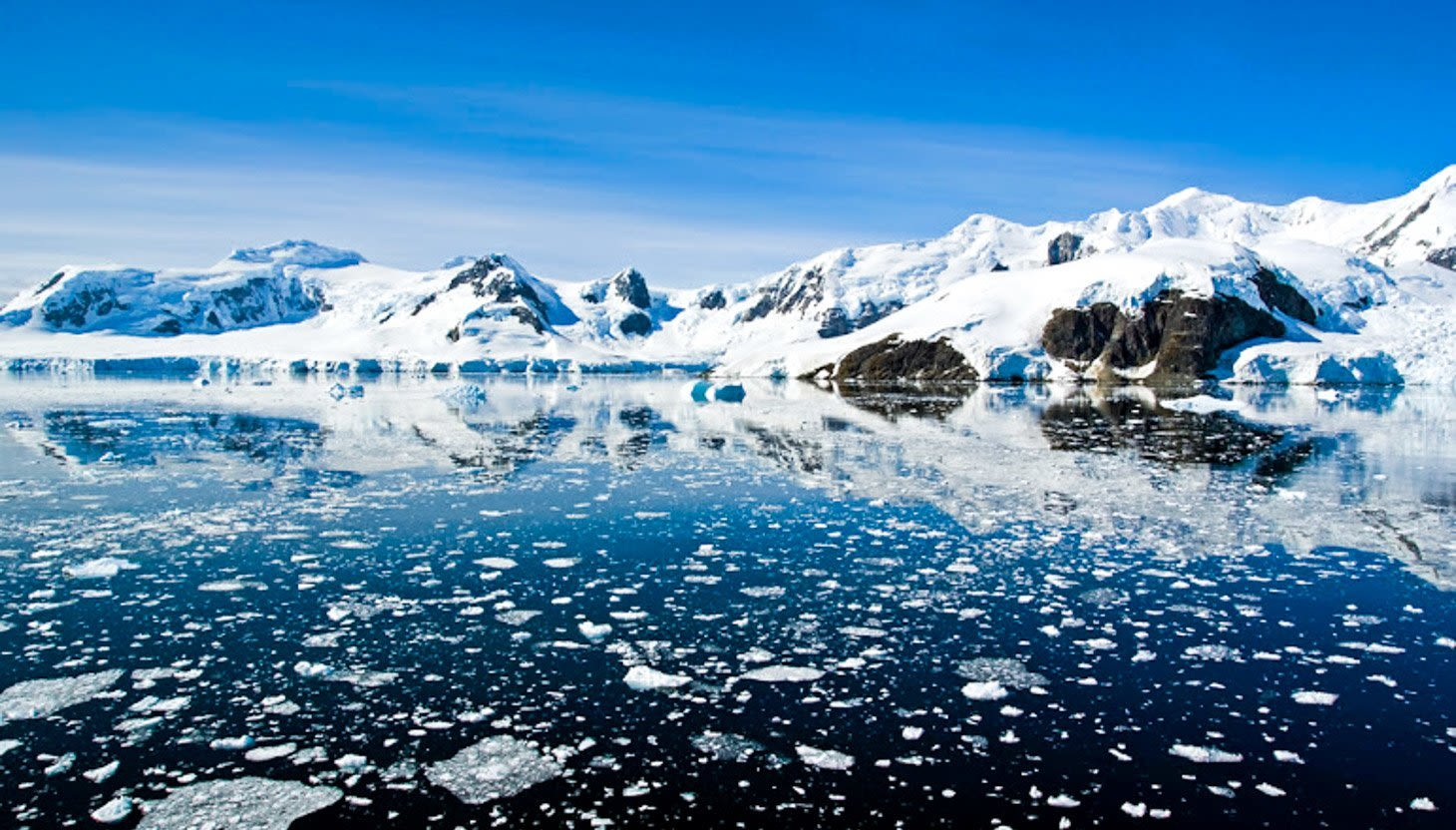 Antarctica mountains on edge of icy ocean bay