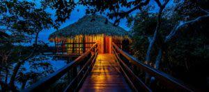 Path through trees to lit amazon jungle lodge bungalow at night