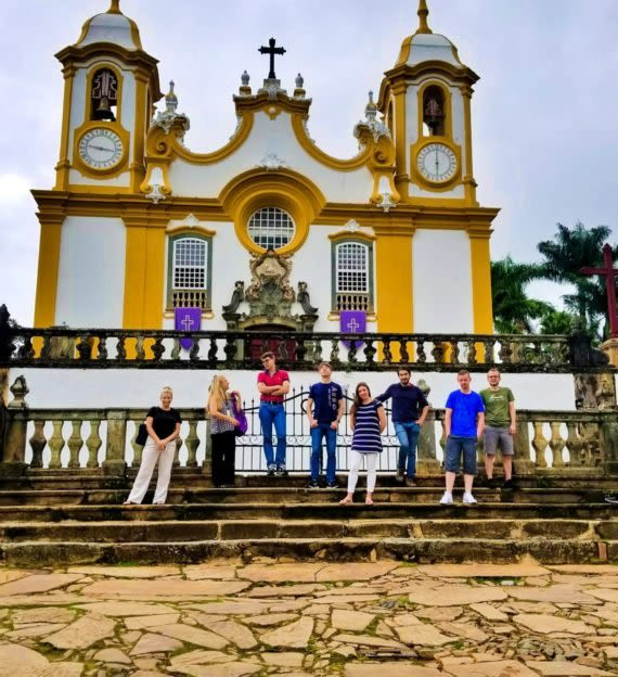 SAT team stands on steps in front of South America church