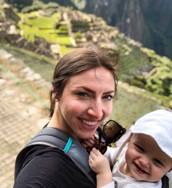 Woman holds baby on top of Machu Picchu