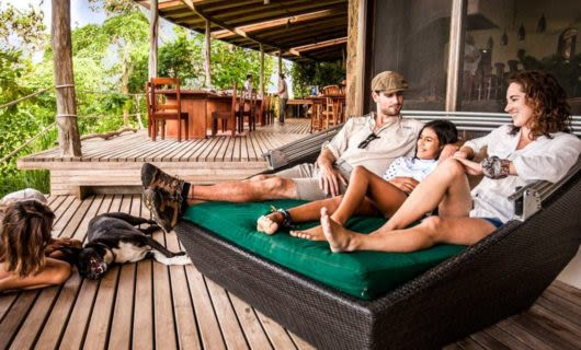 Family lounges on porch in Galapagos