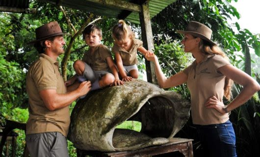 Toddlers climb on tortoise shell while parents watch