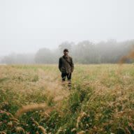 young man standing in the middle of a field