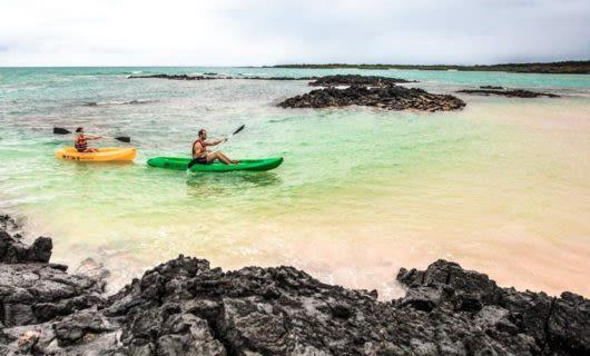 Two kayakers paddle through shallow Galapagos bay