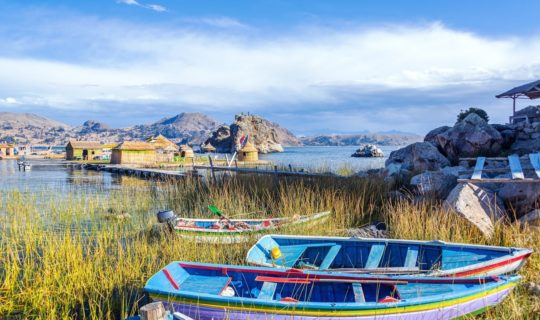 lake-titicaca-with-reed-houses-and-traditional-boats-on-shore