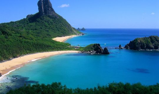 beautiful-island-beach-and-steep-mountain-rising-above-ocean