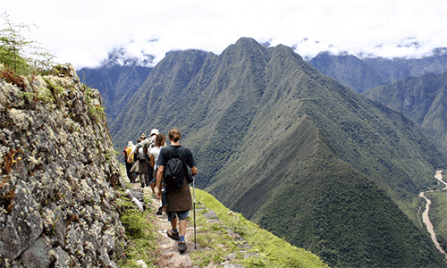 A group hiking the Inca Trail through the mountains and clouds