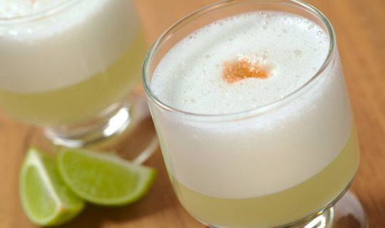 close-up-of-pisco-sour-with-limes