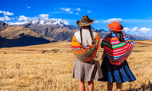 Two native Peruvian girls looking off into the mountains
