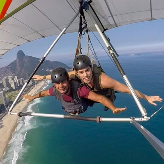 Two men visiting brazil and paragliding over water
