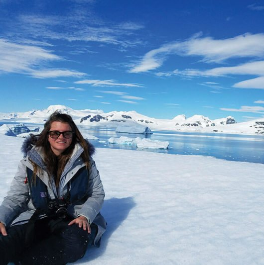 woman sitting in the snow in antarctica