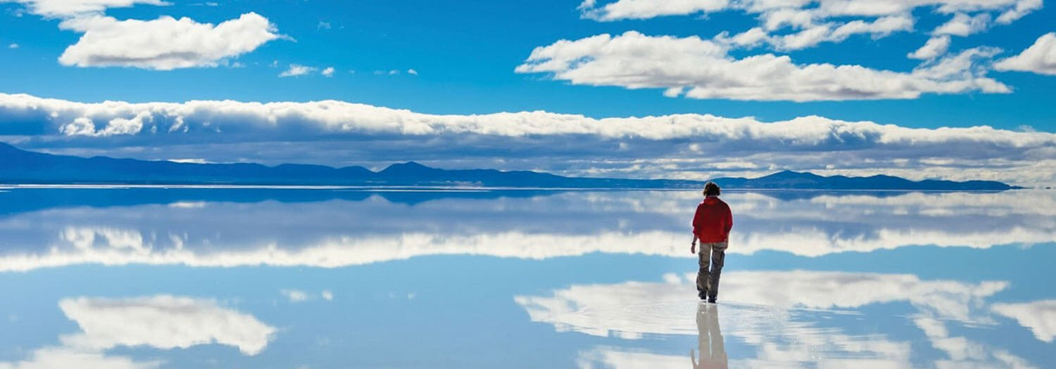 traveler walking on the Uyuni Salt Flats during Bolivia's summer