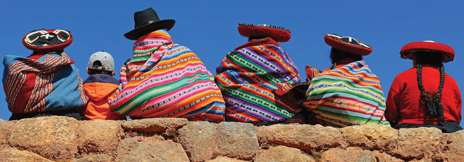 native people in Bolivia sitting on ruins in Winter