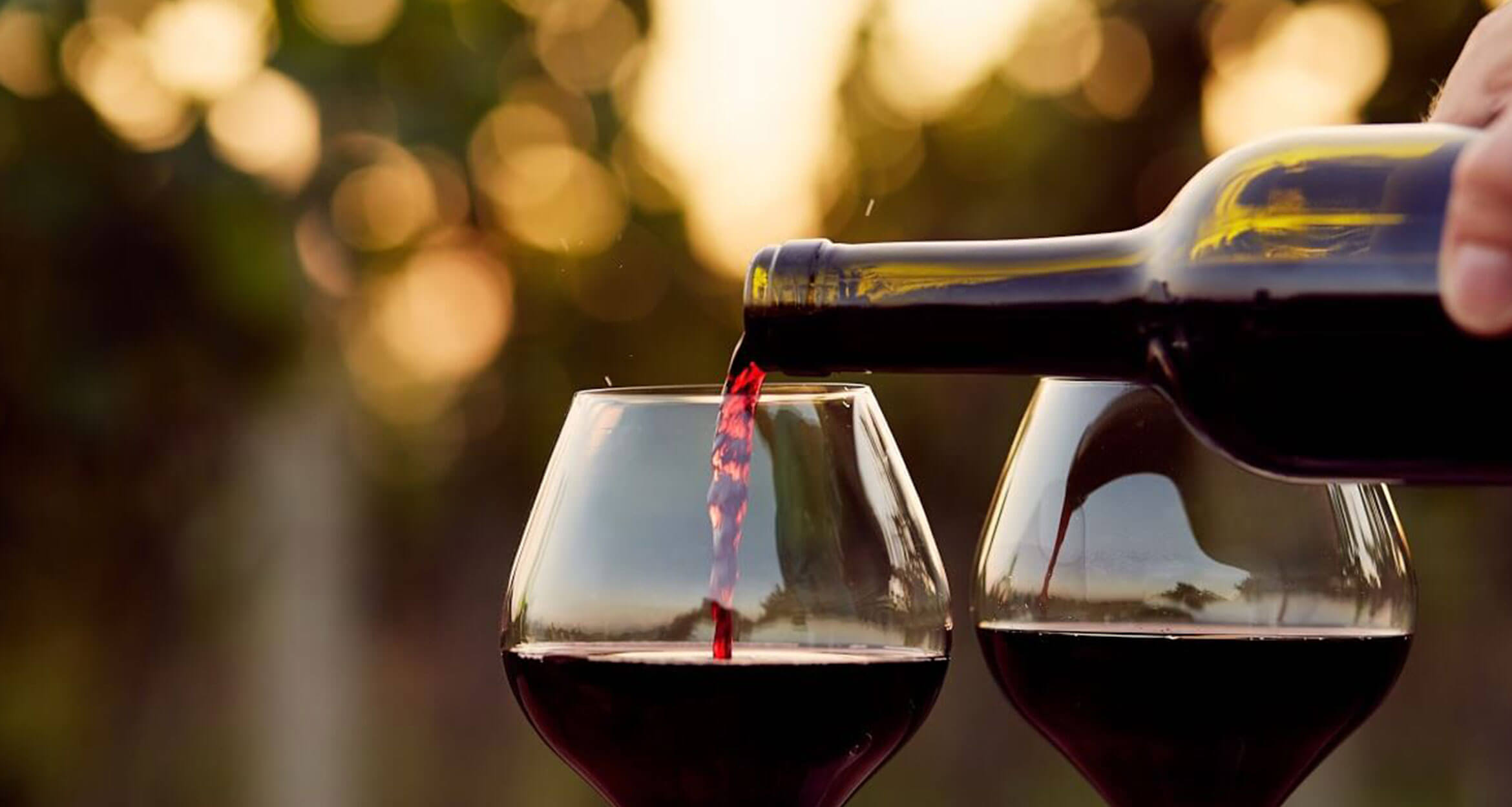 man pouring two wine glasses with red wine