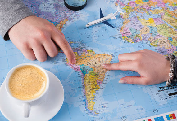 two people planning a south america trip while looking at a map
