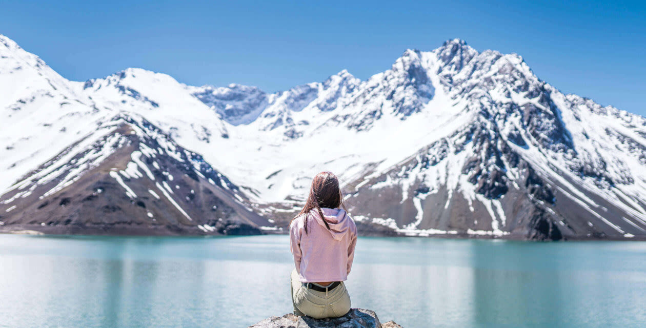 Woman sitting on a rock in the Chilean Mountain range