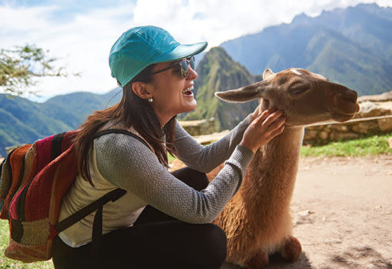 woman petting a llama at machu picchu peru
